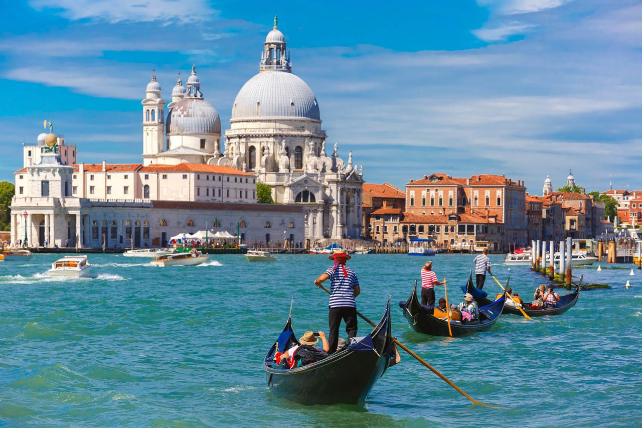 Picturesque view of Gondolas on Canal Grande with Basilica di Santa Maria della Salute in the background, Venice, Italy. Selective focus on Gondolier